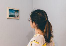 mujer en una galería de arte, observando un cuadro.