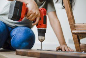 mujer usando taladro en madera
