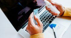 persona limpiando teclado de laptop